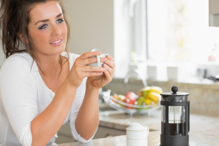 Woman thinking over coffee at breakfast in kitchen photo