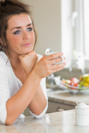 Thinking woman having coffee at breakfast in kitchen photo