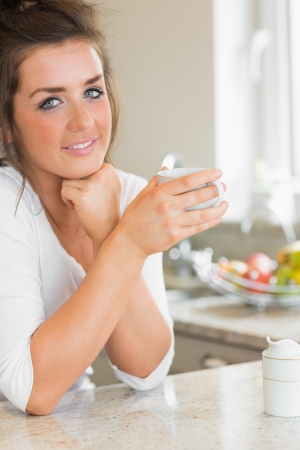 Smiling woman having coffee at breakfast in kitchen photo