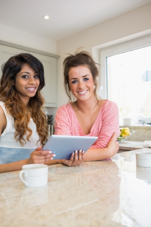 amity: Happy girls with tablet computer having coffee in kitchen
