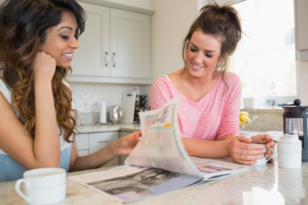Two friends having coffee and reading magazine together in kitchen photo