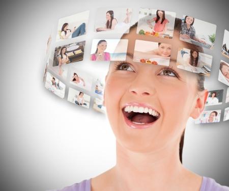 persona feliz: Mujer visualizaci�n de im�genes en la cabeza y sonriendo sobre fondo gris