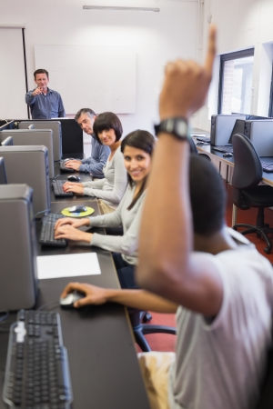 Student raising his hand in computer class photo
