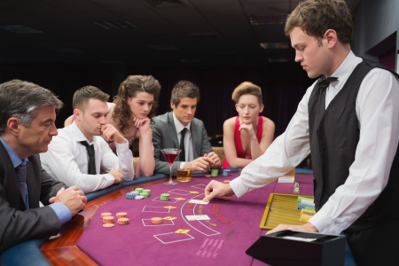 People sitting at table at the casino playing poker photo
