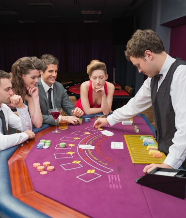 casino dealer: People sitting at table playing poker in casino Stock Photo