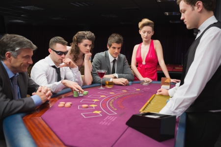 People sitting at table playing poker in a casino Stock Photo - 16065369