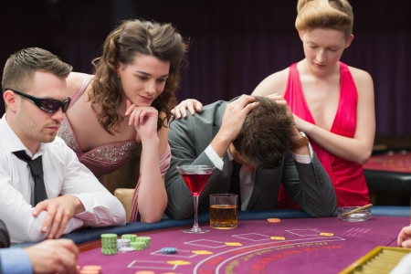 Woman comforting man losing at poker in casino photo