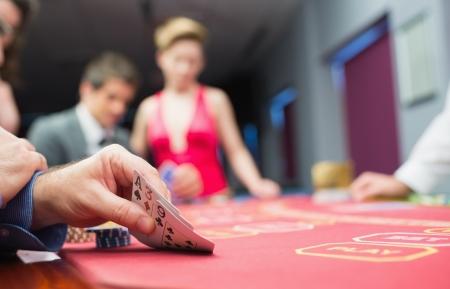 casino dealer: Man lifting hand of poker in casino