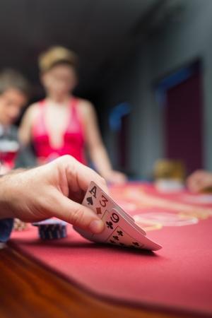 Man lifting poker hand in casino Stock Photo - 16052435