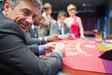 Man smiling at the poker table in casino photo