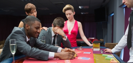 Women comforting man as other man takes jackpot at poker in casino Stock Photo - 16053249