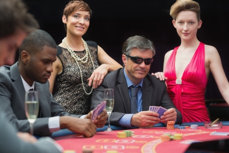 Man in sunglasses playing poker with two women either side in casino photo