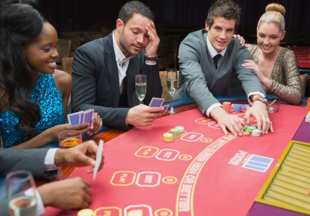 Smiling man claiming the pot in poker game in casino Stock Photo - 16054103