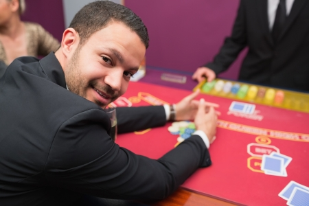 Man looking up from claiming his winnings from poker game in casino Stock Photo - 16066363