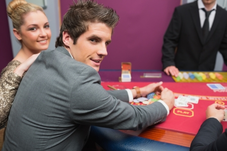 Couple smiling as man is taking his winnings in casino  Stock Photo - 16077929