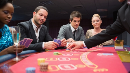 People playing poker at the table in casino photo