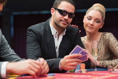 Man in sunglasses showing hand to woman beside him at poker game in casino photo