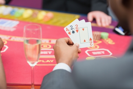 Man holding up poker hand in casino photo
