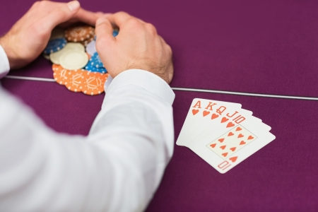 Man winning at poker with royal flush in casino Stock Photo - 16056388