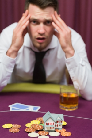 Man losing his house at poker game in casino photo