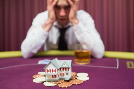 El hombre est� apostando a su casa en el juego de p�quer en el casino photo