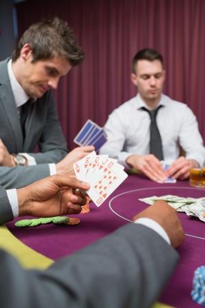 Man at poker table has royal flush in poker game in casino Stock Photo - 16076768