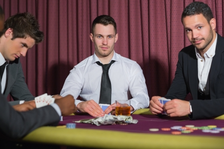 high stakes: Two smiling men looking up from poker game in casino