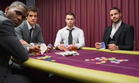 high stakes: Men looking up from high stakes poker game in casino