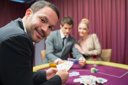 Man smiling and looking up from poker game in casino Stock Photo - 16079186