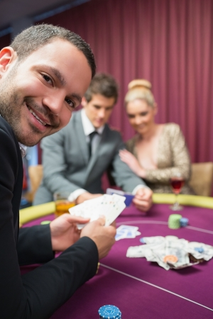 high stakes: Man smiling while sitting at poker table in casino