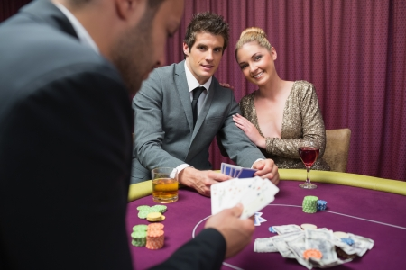 high stakes: Couple playing poker and smiling in casino