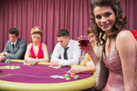 high stakes: Woman smiling at poker table in casino Stock Photo