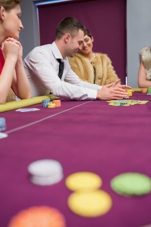 bets: Happy people placing bets at poker game in casino