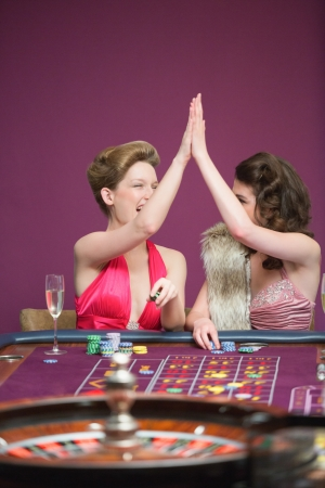 Women high fiving at roulette table in casino photo
