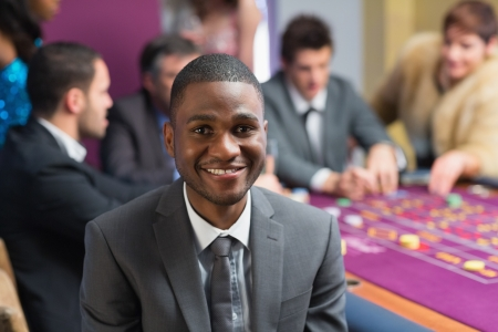 Smiling man sitting at the casino at the roulette table photo
