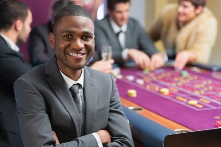 Smiling man sitting at the casino arms crossed at roulette table Stock Photo - 16079533