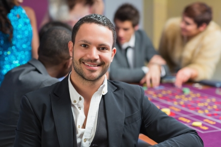 Smiling man sitting leaning on roulette table in casino Stock Photo - 16079357