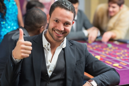 Smiling man thumbs up at the casino at roulette table photo