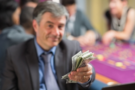 Man holding out money at roullette table in casino photo