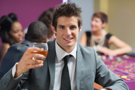 Man raising whickey glass at roulette table in casino Stock Photo - 16075744