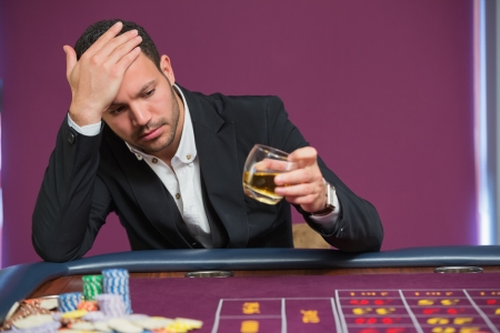 Man looking at whiskey glass at roulette table photo