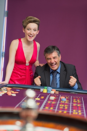 Man and woman cheering at roulette table in casino photo