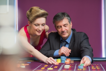 Man and woman placing bets at roulette table photo