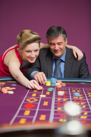 Woman placing bet for man at roulette table photo