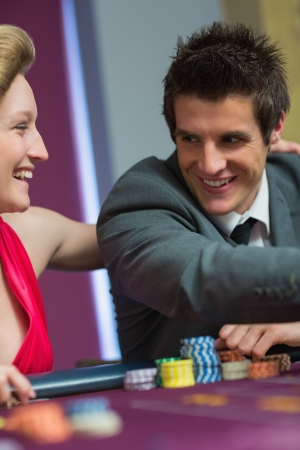 Couple smiling at each other at roulette table in casino photo