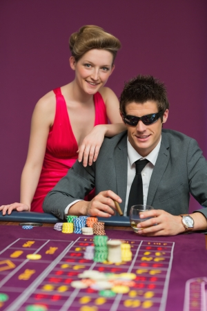 Couple smiling at the table man wearing sun glasses photo