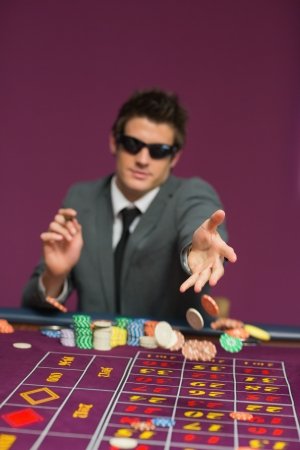 MMan throwing chips on roulette table in casino photo