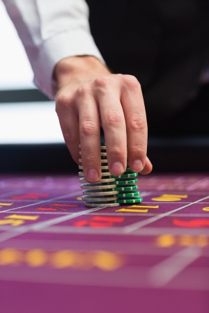 croupier: Dealer placing chips on table in casino Stock Photo