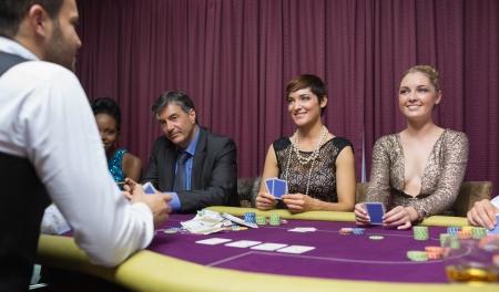 Women smiling at dealer in poker game Stock Photo - 16058323