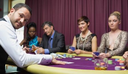 Dealer smiling at poker game in casino Stock Photo - 16051588